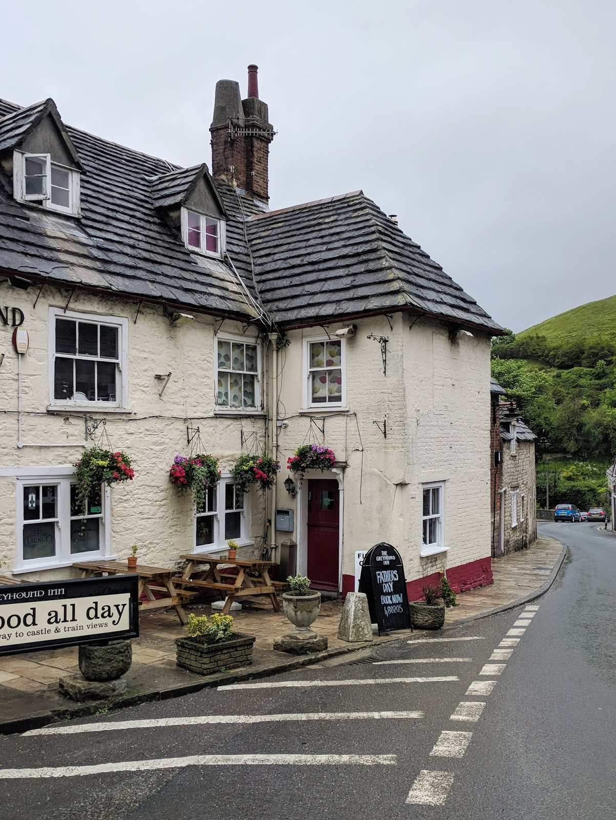 a charming pub in Corfe Castle with hanging plants against a white exterior