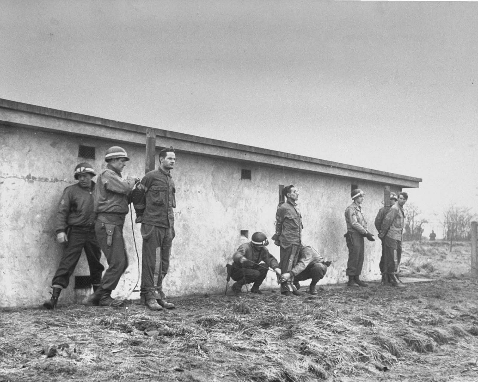 German infiltrators lined up for execution by firing squad after conviction by a military court for wearing U.S. uniforms during the Battle of the Bulge. December 23, 1944.