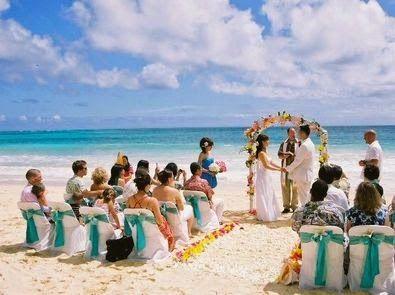Boda en playa con invitados sentados en sillas. El cura casando a los novios que están bajo un arco de flores. El mar de fondo