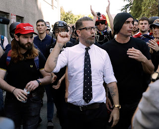 Gavin McInnes, center, founder of the far-right group Proud Boys, is surrounded by supporters after speaking at a rally in Berkeley, Calif. McInnes and his Proud Boys group have been banned from Facebook and Instagram because of policies prohibiting hate groups.(AP Photo/Marcio Jose Sanchez, File)