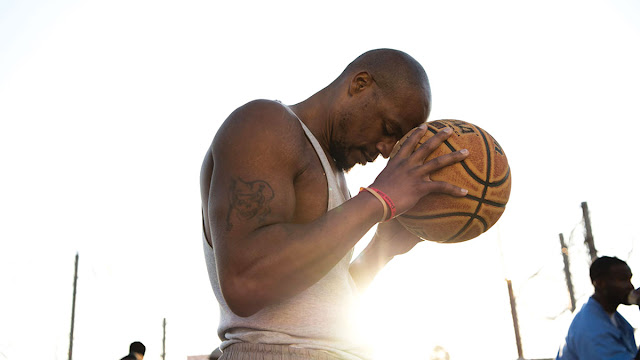 a man prays to a basketball
