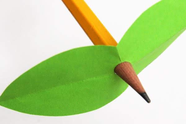 masukkan ujung bawah paku kayu, pensil yang tidak diraut, atau batang jerami minum melalui lubang pada sepasang daun