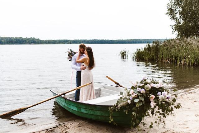Stylizowana sesja zdjęciowa, Młoda Para w łodzi przystrojonej kwiatami, sesja zdjęciowa, romantyczny rejs, podróż poślubna, sesja ślubna, małżeństwo, talk about love, suknia ślubna, bukiet ślubny, jezioro, lato