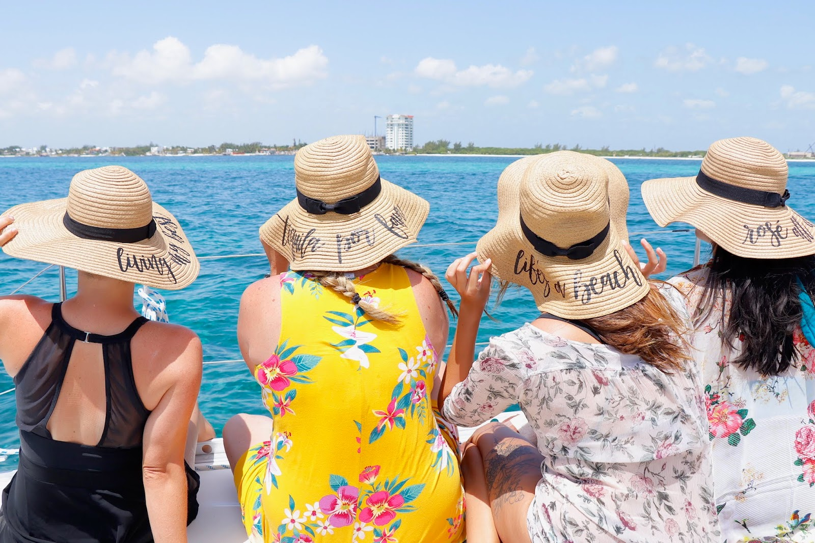 four women look out over the gulf of mexico wearing floppy beach hats with cute sayings