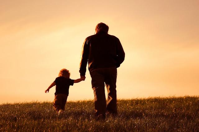Imagen de un padre caminando de la mano con su hijo