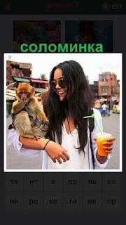 женщина на руках держит обезьяну и в другой сок с соломинкой