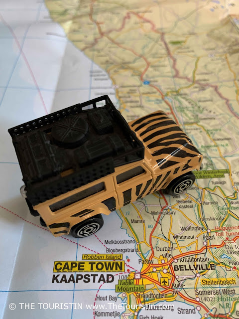 A beige and black painted toy Land Rover on a paper map next to the words Cape Town.