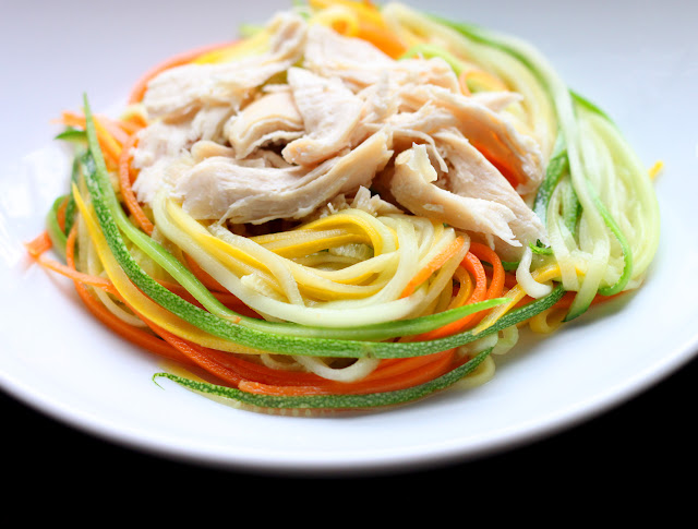 Shredded chicken and zucchini noodles in a white bowl for Zucchini Noodles with Chicken and Tangy Peanut Sauce
