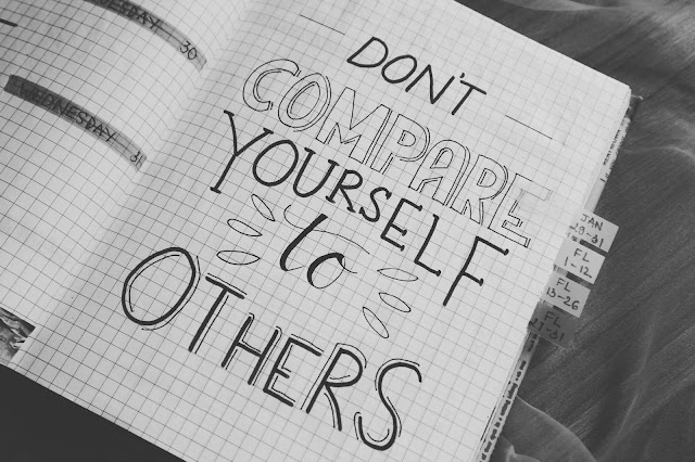 Open notebook with writing that says don't compare yourself with others