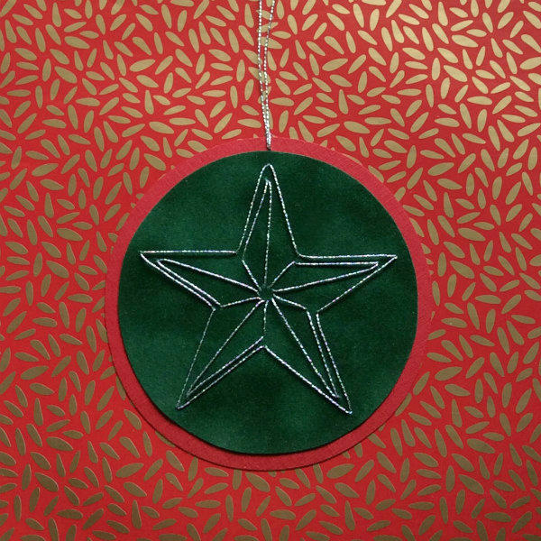 stitched star on circular paper ornament displayed on red and gold wrapping paper