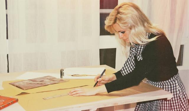 Alejandra Colomera vestida con jersey negro, falda de tablas cuadros vichy y lazo en el cuello vichy haciendo patrones de costura