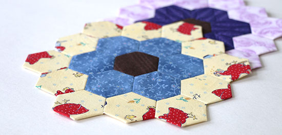 Angled view of two hexagon flower blocks, one in bright primary colors and the other in purples, on a white background.
