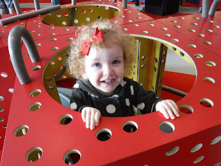 a strawberry blonde toddler peeks out of a large red cube with many holes in it at the Sioux City Art Center's Junior League Hands-On Gallery