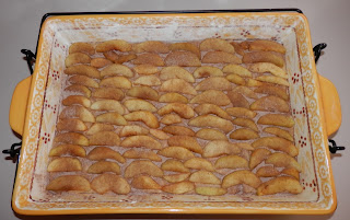 A layer of apple slices sprinkled with cinnamon sugar while assembling an Apple Coffeecake
