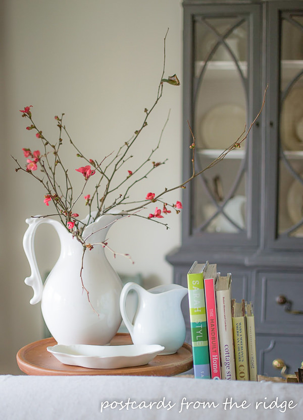 quince branches in a white ironstone pitcher