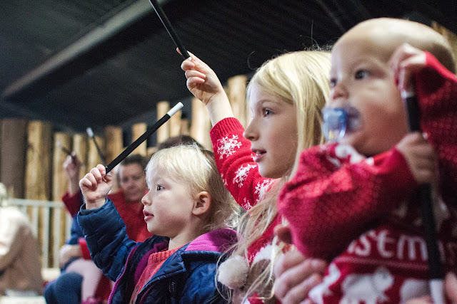 Children of all ages waving magic wands and looking intently forwards at Elf Academy