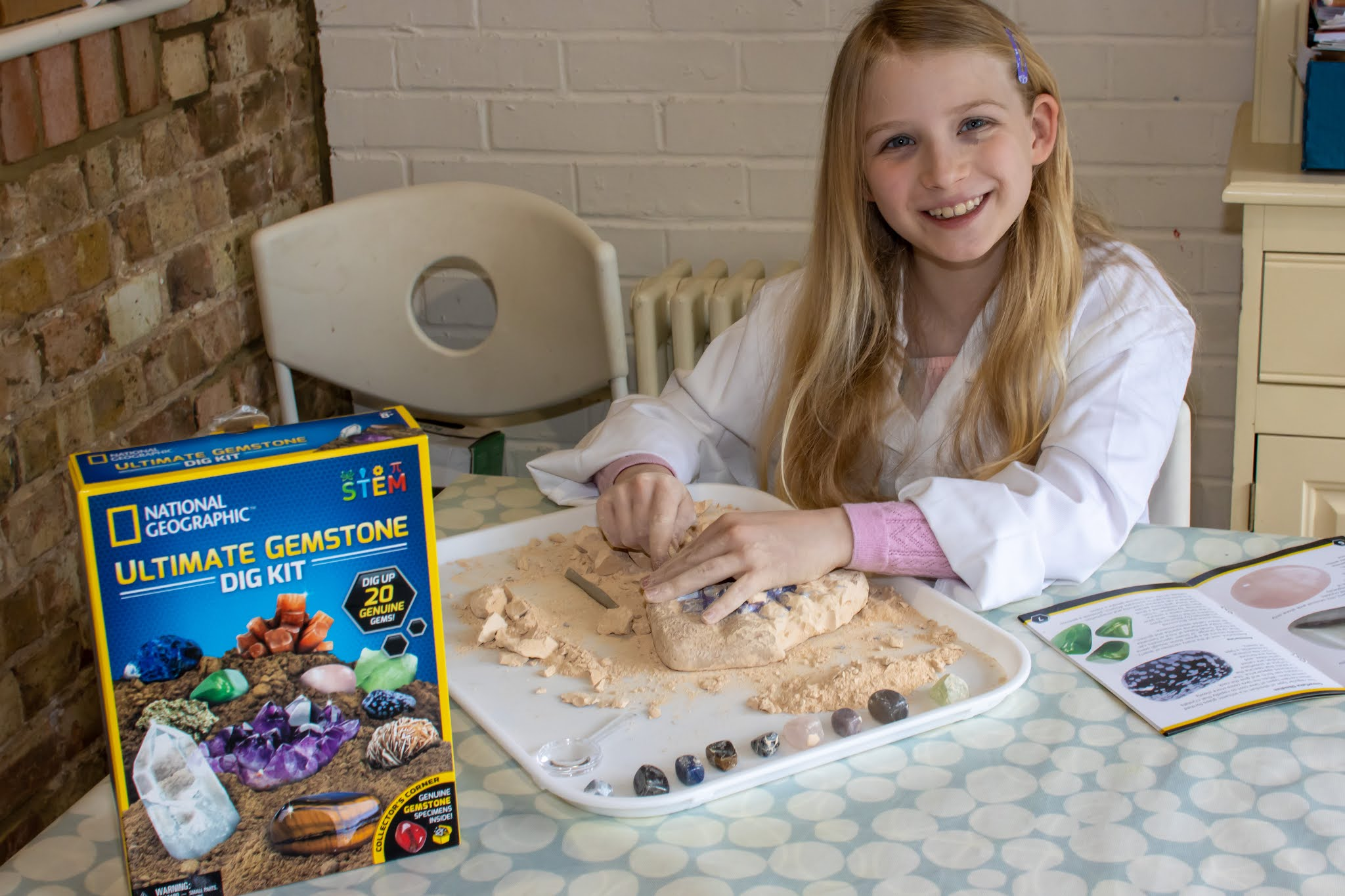 A smiling 9 year old girl in a lab coat digging gemstones out of a block from the Ultimate Gemstone Dig Kit she is reviewing