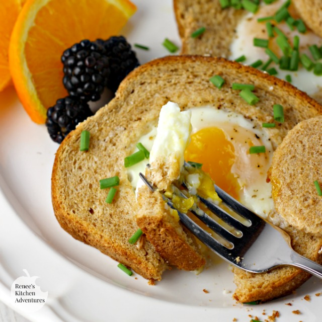 Baked Eggs in a Basket by Renee's Kitchen Adventures on a plate with fruit and a fork with a bite on the tip