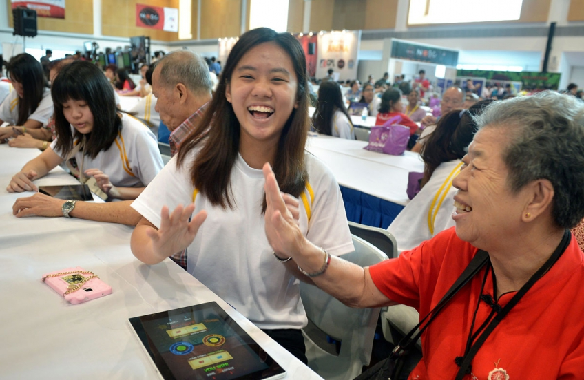 ITE student Celine Si, 19, playing Fruit Ninja with retiree Ng Geok Heok, 70, who was among 50 senior citizens invited to the Institute of Technical Education College Central yesterday.