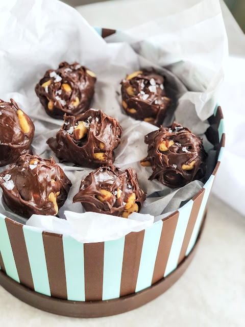 chocolate peanut clusters sprinkled with salt and boxed in white tissue paper
