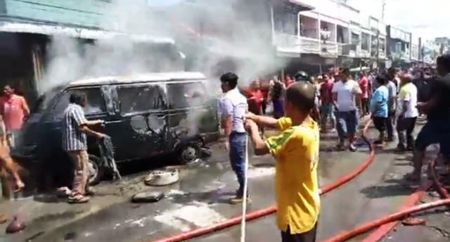 Petugas pemadam kebakaran dan warga memadamkan api yang membakar mobil.