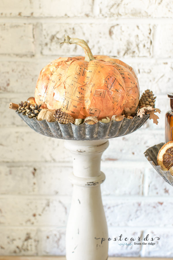 paper mache pumpkin on diy pedestal stand made from wooden candleholder and tart pan