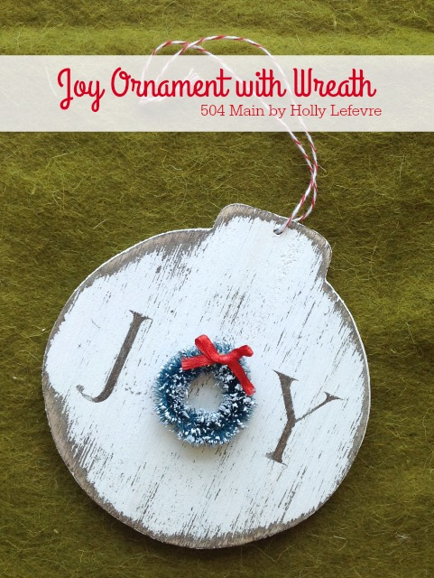 A handmade wood ornament adorned with a wreath.