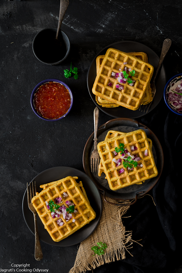 These savoury waffles served on a black plate, topped with chopped re