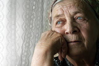 Closeup of the sad face of a senior citizen at a window.