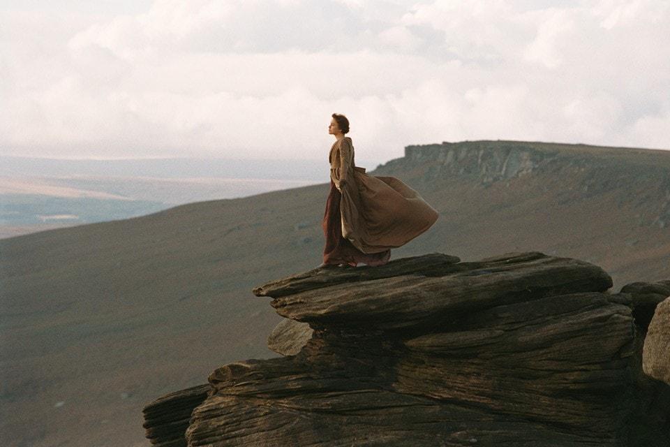 silhouette d'une femme dans le vent sur le sommet d'une colline
