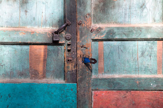 A beautifully colored door detail showing red and green paint and rusted locks from a door in Guilin, China.