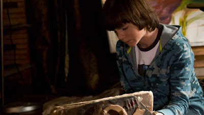 Chandler Riggs reads a forbidden book in a movie still for the 2014 horror thriller film Mercy