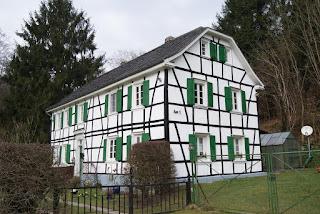 Ein weiß gestrichenes Fachwerkhaus mit grünen Fensterläden steht am Waldrand.