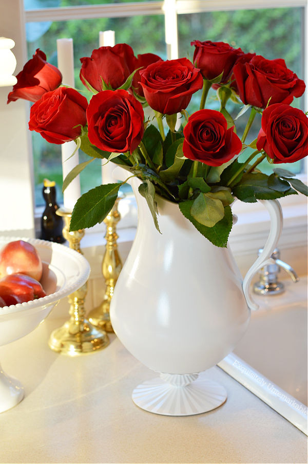 White pitcher filled with red roses on kitchen countertop