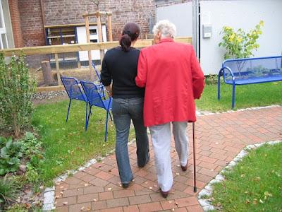 Kvinnlig skötare som leder en äldre kvinna i armen, sedda bakifrån.