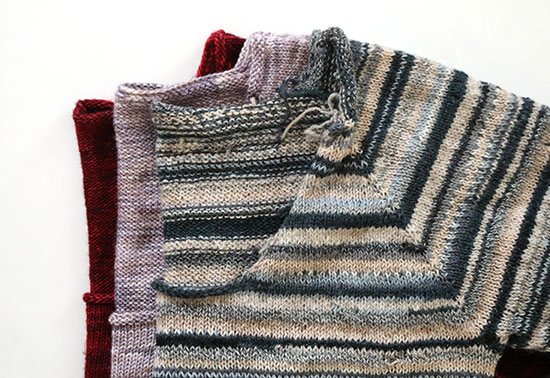 Side view of the necklines of three sweaters, showing the variation in the depth of each neckline.
