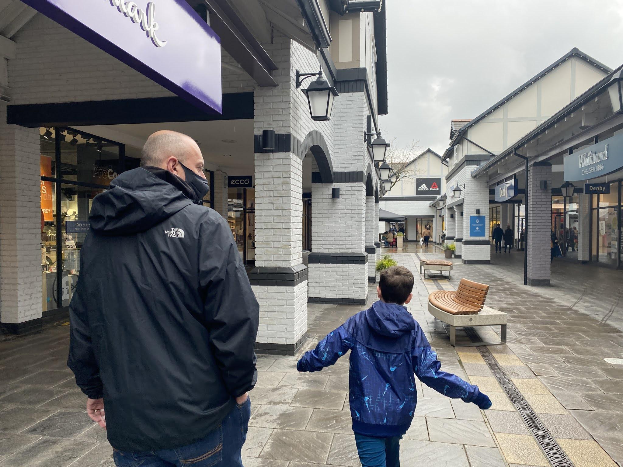boy and man walking through the shopping centre.