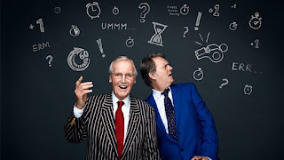 Nicholas Parsons and Paul Merton in front of a blackboard