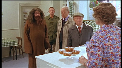 """Hywell Bennett (""""Kevin""""), in a potato sack and fake beard, with Truly, Clegg, Billy Hardcastle and Ivy in the Cafe. There are buns on the counter."""