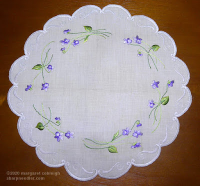 Filament silk used to stitch Society Silk violets under brigt lighting showing how it glows