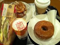 il vassoio con succo d'arancia, cinnamonroll, sandwich e donuts