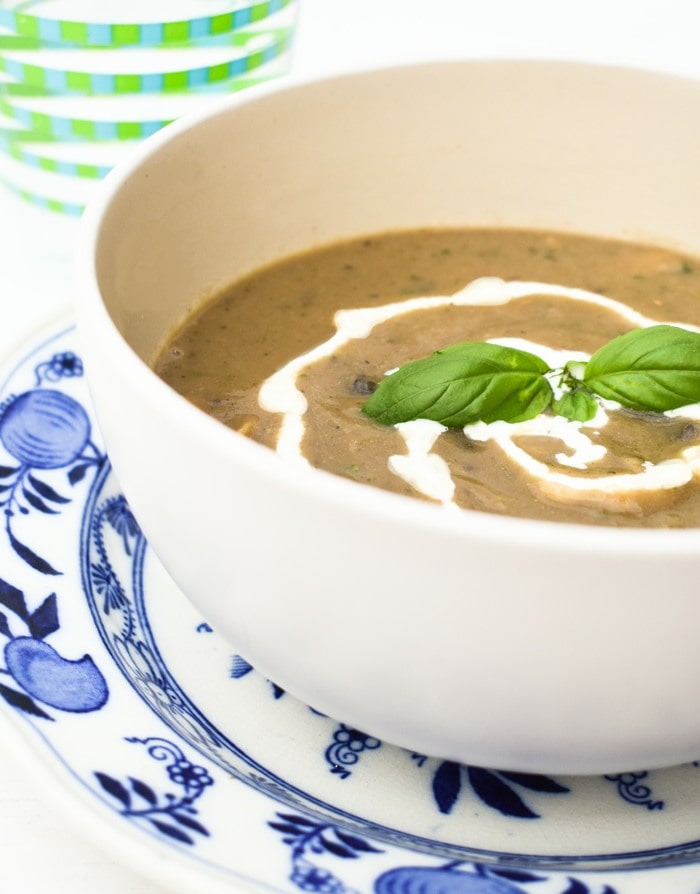 Close up of  bowl of mushroom soup with swirl of cream, next to a stripy glass of water