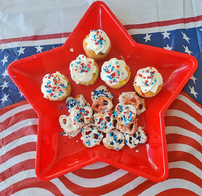 this is a red star dish with white chocolate dipped pretzels and funfetti cupcakes
