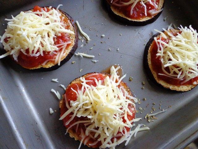 Cover each eggplant round with one spoon of chopped tomatoes, sprinkle with oregano and basil leaves, top with grated cheese and bake an