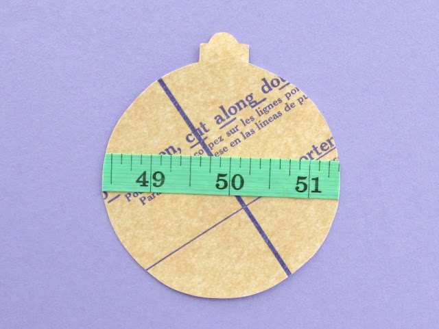 Paper bauble decorated with sewing pattern and measuring tape
