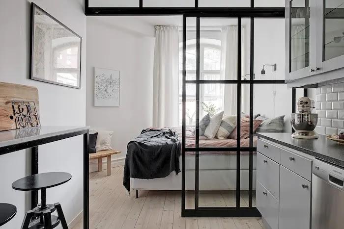Puerta corredera de vidrio y hierro entre la cocina y el dormitorio de un apartamento pequeño