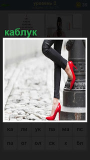 Красный женский каблук уперся в фонарный столб, ноги в черных джинсах