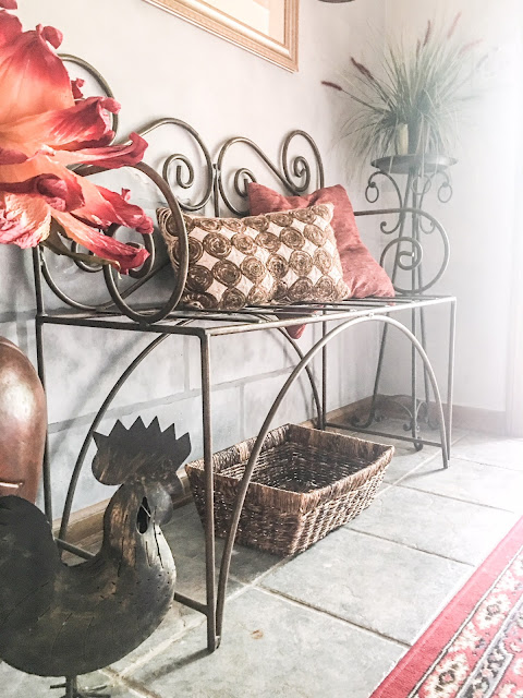 metal bench with red decor in entry way