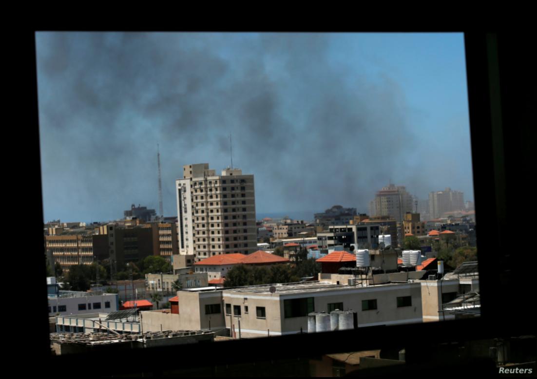 Vista de una ventana, el humo se alza sobre los edificios de la ciudad de Gaza tras los enfrentamientos, el 13 de mayo de 2021 / REUTERS