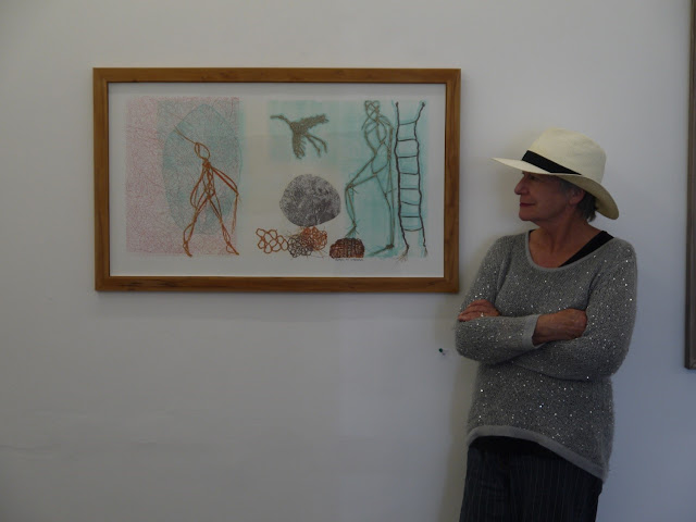Woman with a hat on leaning against a wall looking at a painting.